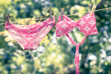 Retro tone image of cute bikini bathing suit hanging on a line to dry