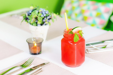 Fresh watermelon juice in jar with straw on white table with candle on the green background. Shallow depth of field, isometric composition.