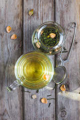 Mug of flavored green tea with rose buds and petals