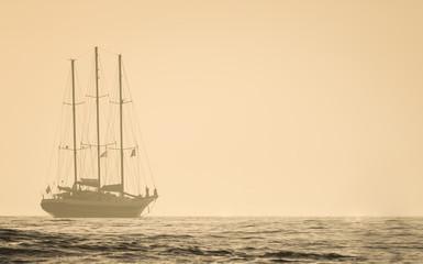 Foggy sunset sailboat at sea