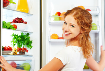 Happy woman and open refrigerator with fruits, vegetables and he