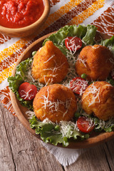 rice balls stuffed with meat and tomato sauce closeup. Vertical