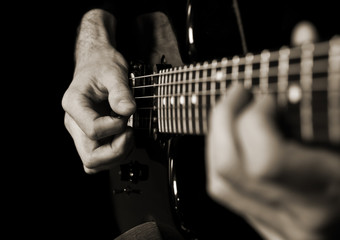 Hands of man playing guitar in dark colors