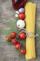 Pasta spaghetti, onion, garlic and tomato on wooden background