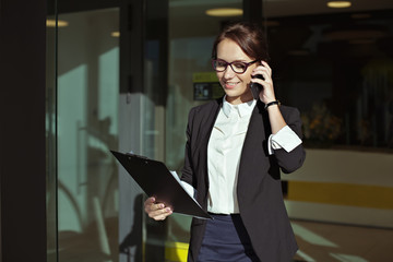 Business people concept- image of a business woman who goes out of office, talking on the phone with the documents in the hands. Beautiful business lady manager with documents.