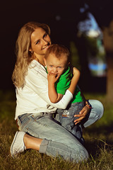 Happy Mother hugging her little son in park. Young mum and little child on relaxing and smilling in park on sunset.