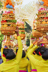 Procession of beautiful Balinese women in traditional costumes carry ritual offerings on heads for Hindu ceremony. Arts festival, culture of Bali people, and Indonesia islands. Asian travel background