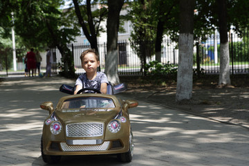 Child driving a toy car