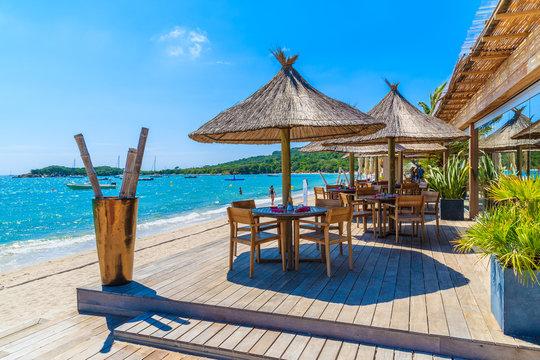 Restaurant tables on beautiful beach in Saint Cyprien coastal town, Corsica island, France