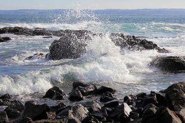 Ocean waves hitting rocks on cliff shore