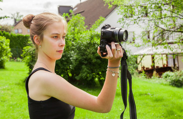 Teenager girl while photographing in the garden