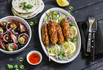 chicken kebab, salad with tomatoes, onions and olives, homemade tortilla is a healthy and delicious meal, on a dark wooden background