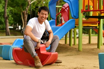 Man playing rocking horse at playground