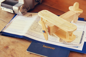 image of flying ticket wooden airplane and passport over wooden table
