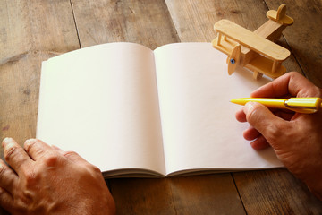 open blank notebook and man hands next to toy aeroplane on wooden table