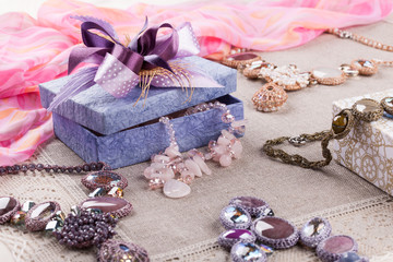 Female jewelry and gift box on linen tablecloth