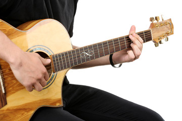 Young man playing on acoustic guitar isolated on white