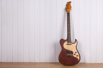 Electric guitar on white wooden wall background