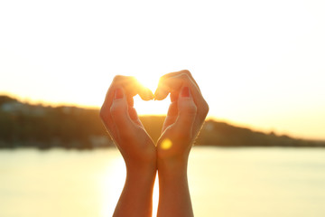 Female hands in shape of heart on sunny sky background