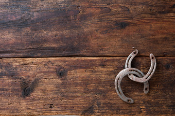 Two old rusty horseshoe on vintage wooden board
