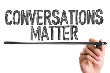 Hand with marker writing the word Conversations Matter