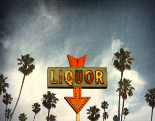 aged and worn vintage liquor neon sign with palm trees