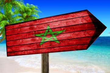 Maroco Flag on wooden table sign on beach background