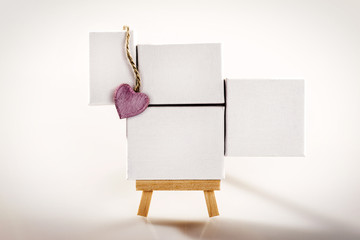 Little tripod wood easel with four white canvas and pink heart.