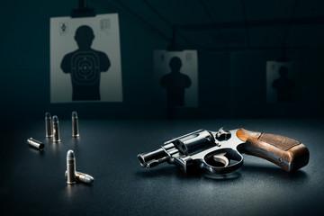 gun sitting on a table at a shooting range / dramatic lighting Wall mural