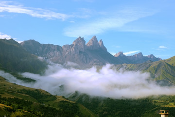 Early morning clouds lying at the foot of les aiguilles d'arves in the french Alps