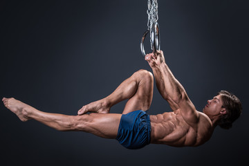 Foto op Plexiglas Gymnastiek Strong gymnast guy on the rings