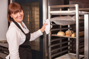 Cheerful saleswoman is working in bakery with joy