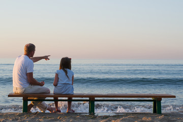 father and daughter looking at the sea