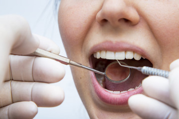 Young female having her teeth examined