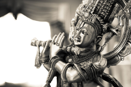 Black and white statue of the Hindu God Krishna playing a flute