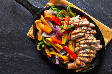 Wall Mural - mexican grilled chicken fajitas in iron skillet shot from overhead on slate