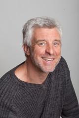 older man sitting smiling