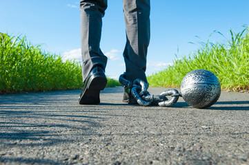 重たい鉄球が付いているビジネスマンの足