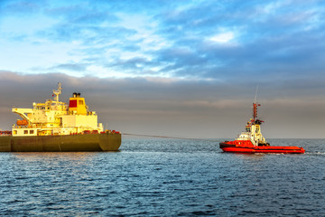 Tugboat pulling the tanker at sea in the morning.