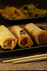 Baked spring rolls with vegetables on a black plate