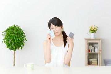 スマートフォンを持って泣く女性