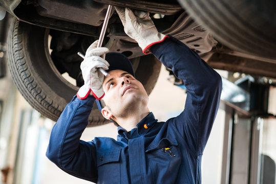 Mechanic repairing a lifted car