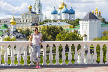 Young Woman in Sunglasses with Trinity Sergius Lavra in Sergiev