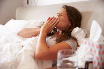Woman Suffering From Cold Lying In Bed With Tissue