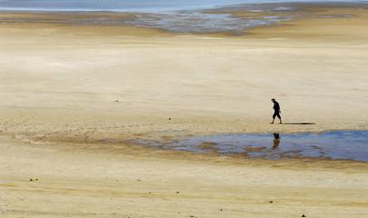 Man walks on dry lake bed