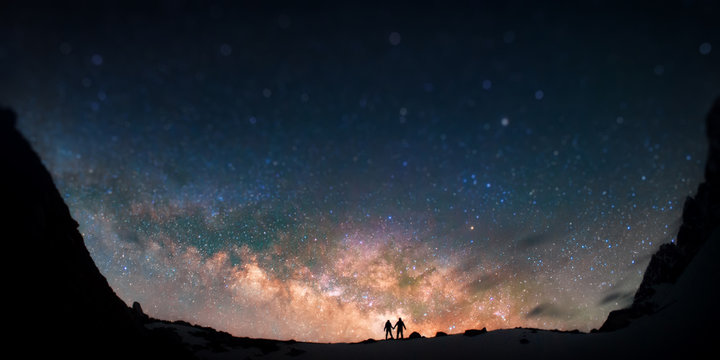 Universe for two. Two people are standing together holding hands against the Milky Way in the mountains.