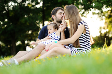 Young family relaxing in the park on the grass. Mom and dad kiss