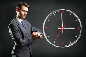 Manager schaut mahnend auf die Uhr