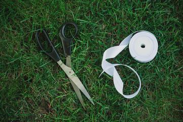 Satin white ribbon and scissors on grass