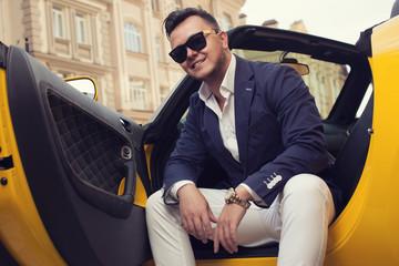 Stylish man sitting in sport car